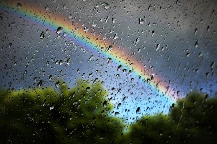 雨でぬれた窓ガラスと虹