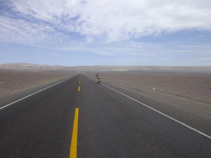 遠くまで伸びる道路上を移転者で進む人