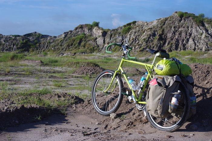 岩肌が剥き出した山のそばに停められたたくさん荷物が乗った自転車