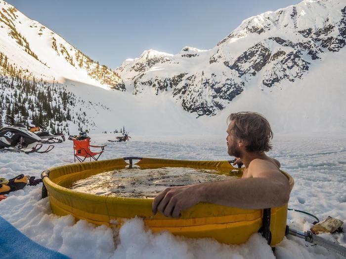 雪山でオリジナル・ノマドの折りたたみ式バスタブに浸かる男性