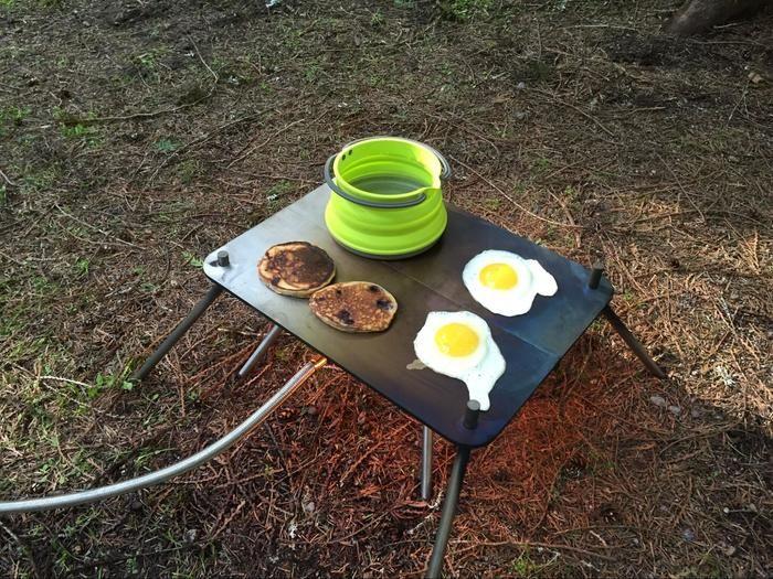 ポケット・キャンプファイヤーにグリドルを載せて料理をする様子