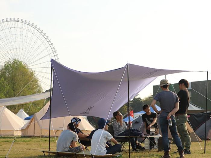 キャンプ場に張られたドッペルギャンガーのタープの下で語らう男性たち