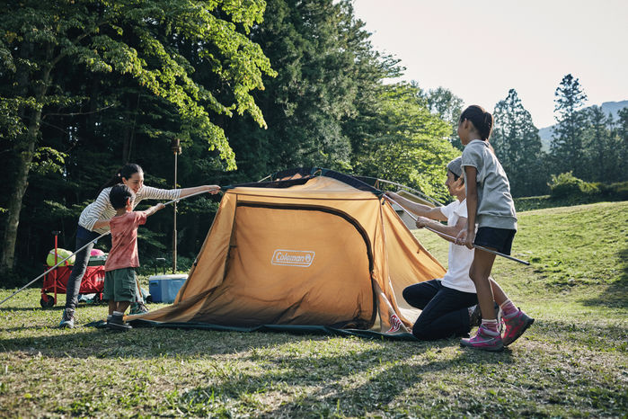 コールマンのテントを立てる家族