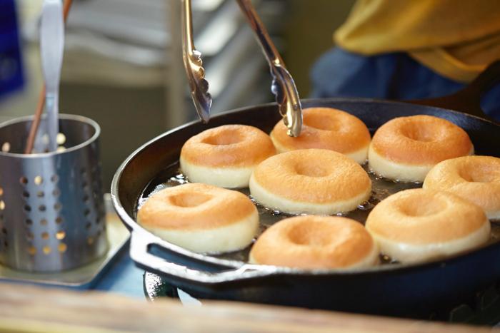 タイニーガーデンフェスティバルないで販売されるHIGUMA DOUGHNUTSの調理の様子