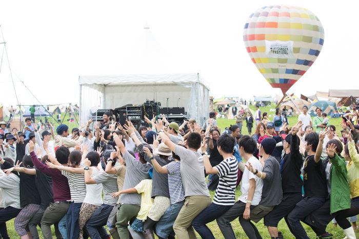 タイニーガーデンフェスティバルで音楽に合わせ大人も子供も一緒にヨガを行う様子