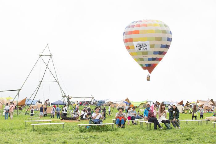 タイニーガーデンフェスティバルの気球とベンチでくつろぐ人々