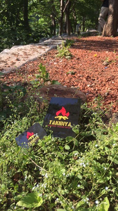 外の草むらに置かれたTAKIBIYAの看板