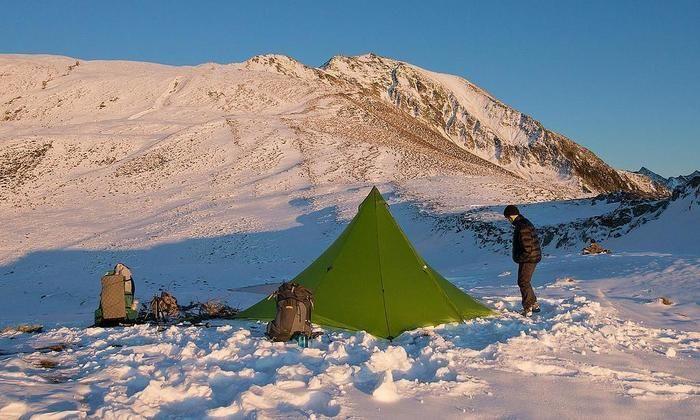 雪山でテントを張ってキャンプをする男性