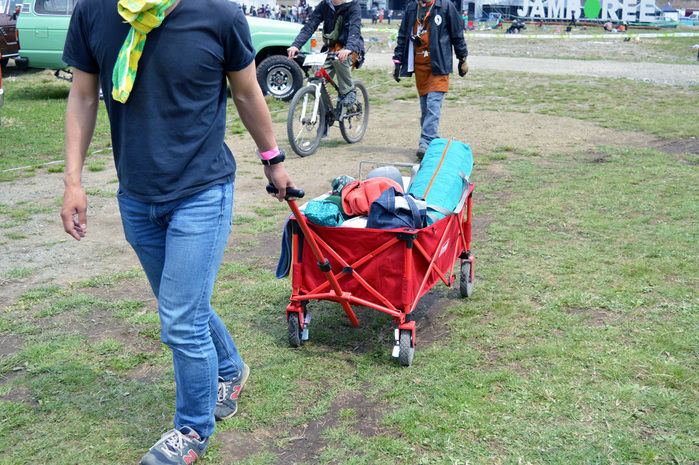 アウトドアワゴンで荷物を運ぶ男性
