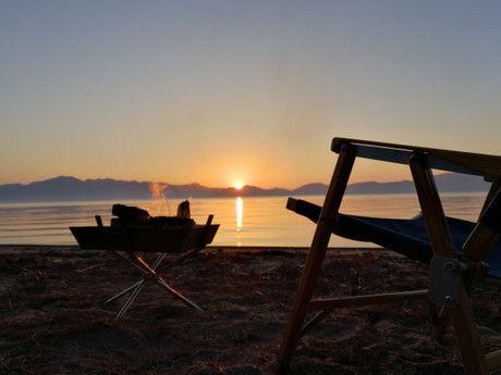 夕日の沈む池の水平線と焚き火とチェア
