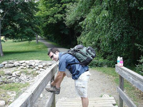 ハイキングコースで靴ひもを結ぶ男性