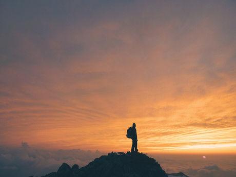山頂から夕陽を眺める人
