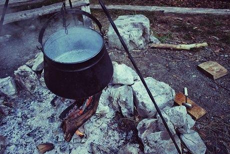 吊るした鍋を焚き火にかけている様子