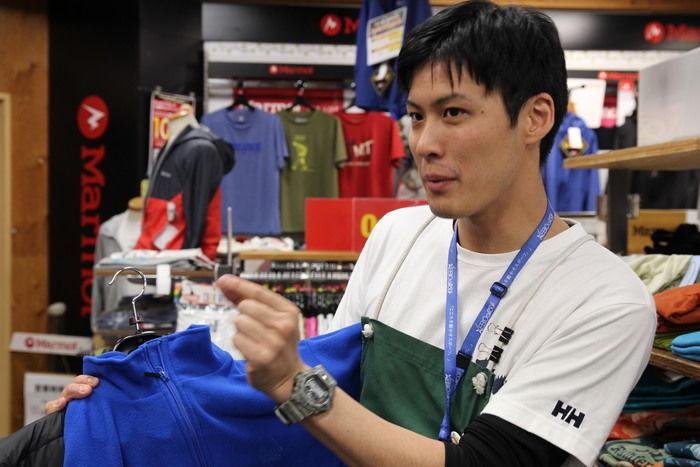 エルブレス新宿店の森岡さんが服の説明をする様子