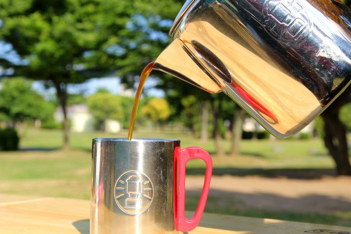 ストレーナーで作ったコーヒーをコップに入れる様子