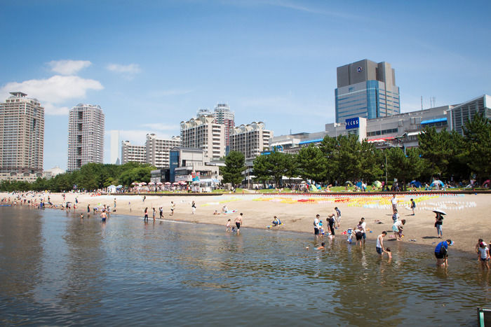 お台場海浜公園の海辺で遊ぶ人たち