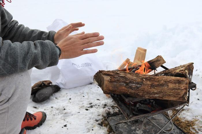 たき火で暖をとる男性