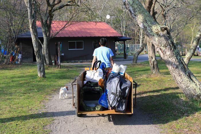 キャンプギアを台車で運ぶ男性