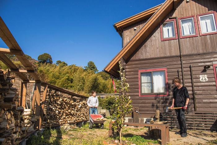 ハウスの裏で薪を着る人
