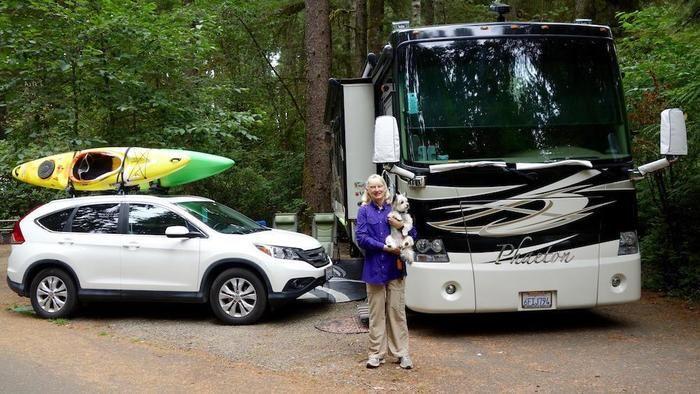 キャンプサイトでペットを抱いている女性