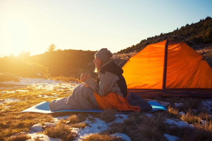 山中のキャンプで朝日に照らされている女性