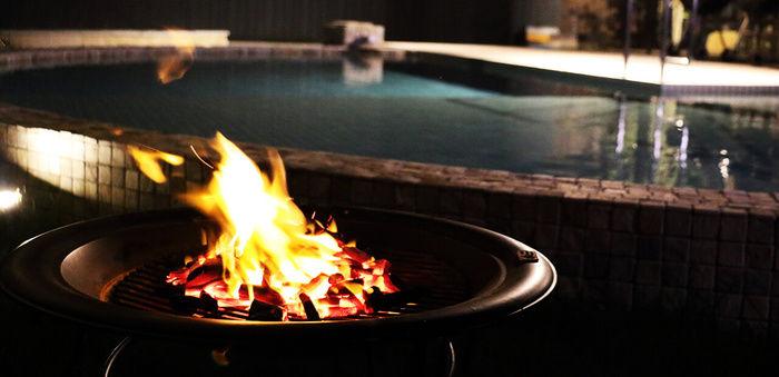 プールサイドで焚き火をする様子