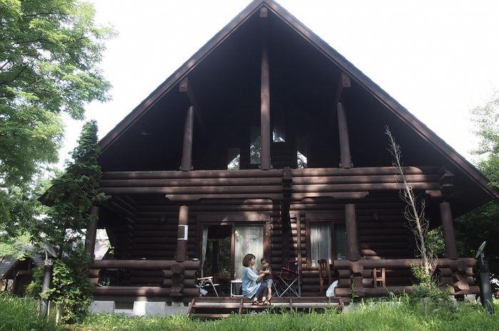三角屋根のコテージと親子