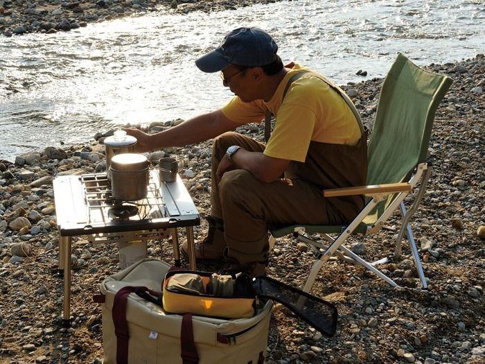 河原でスノーピークのアイアングリルテーブルを使用している様子