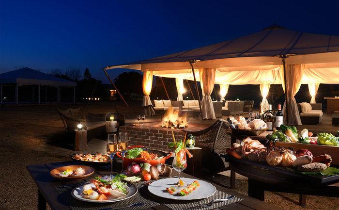 机に並んだ豪華なアウトドア料理と夜のグランピング風景