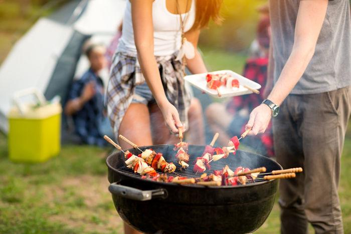バーベキューで串焼きを楽しむ人々の手元