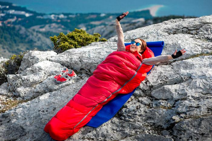 岩の上で寝袋で寝ている女性