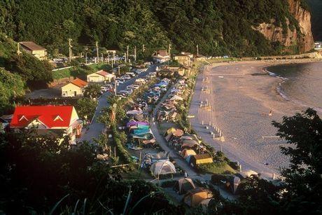 宇久須キャンプ場に並ぶ夕日に照らされた数々のテント