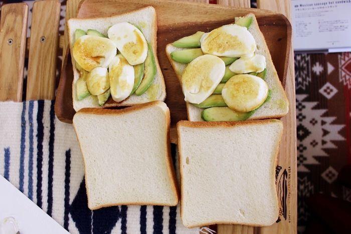 パンの上にアボカドとチーズをのせている様子