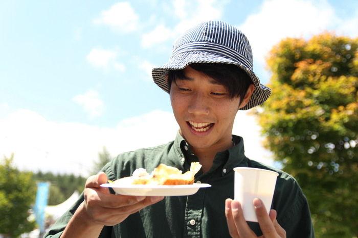 サイトウのゴハンを手に笑顔の男性