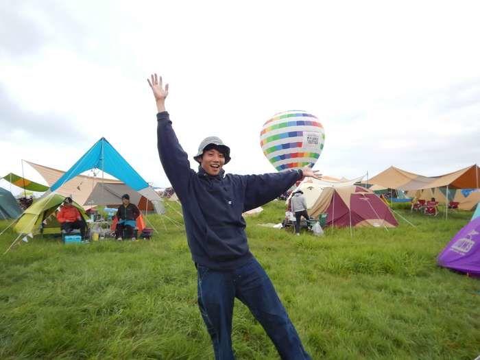 ヨガのポーズをとる男性と空に浮かぶ気球