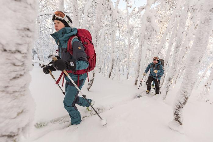 フェールラーベンのウェアを着て雪に覆われた山道を歩く人々