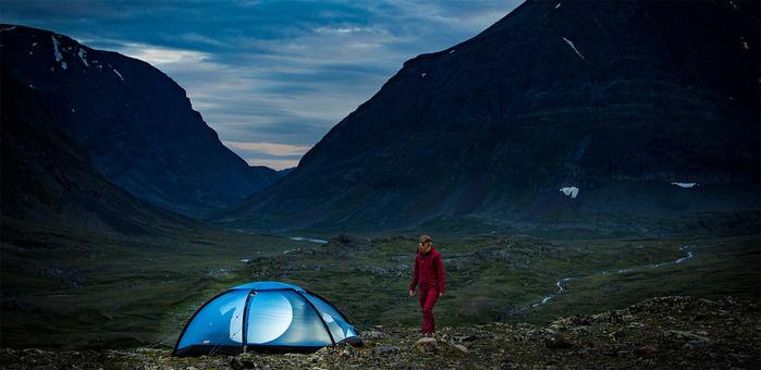 薄暗い山間部で青く光り輝くテントと男性