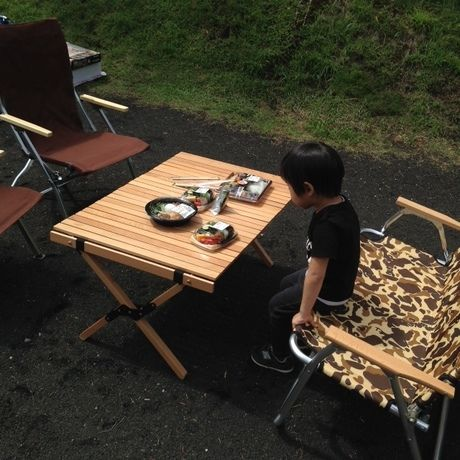 外でお弁当を食べる少年