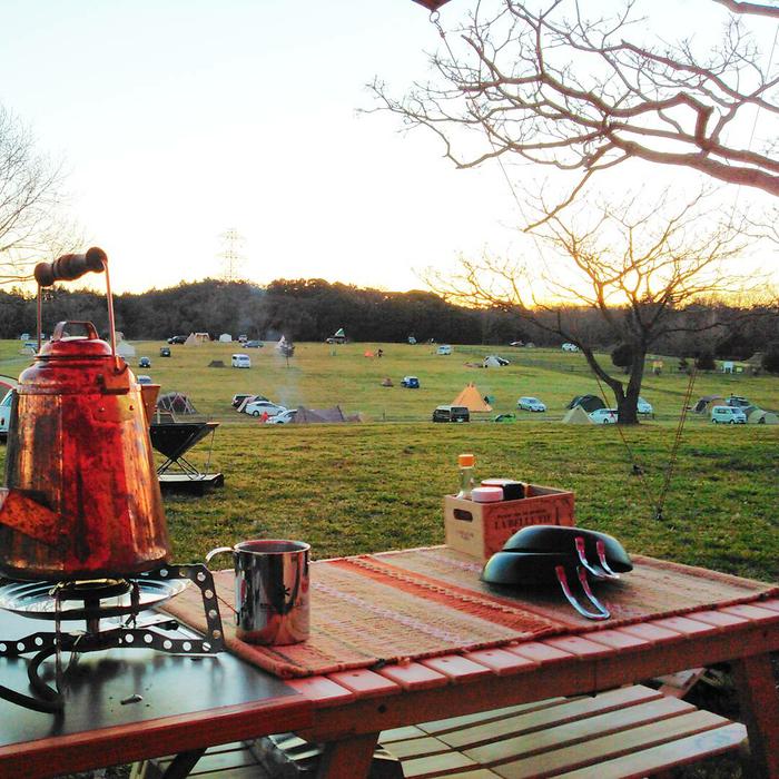 湯気を上げるやかんと芝生のキャンプサイト