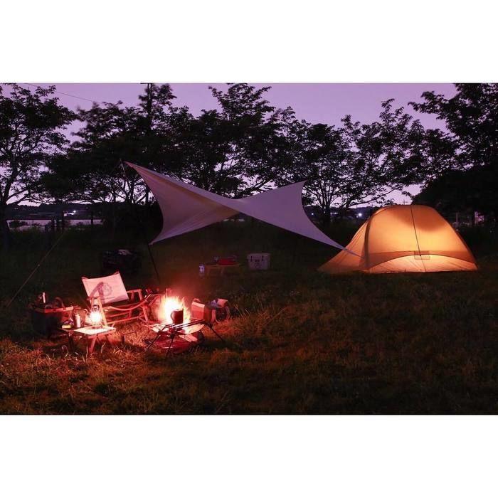 自然の中で焚き火をたいてキャンプを楽しむ様子