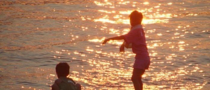 夕日を反射する海辺で遊ぶ少年の後ろ姿