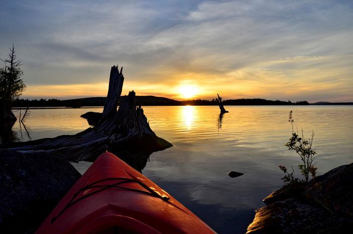 夕暮れの湖に映るカヌー