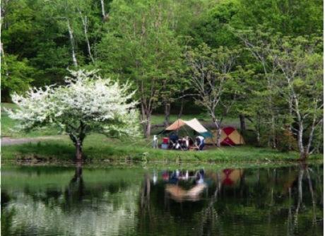 駒出池キャンプ場の湖畔に反射するキャンプサイト