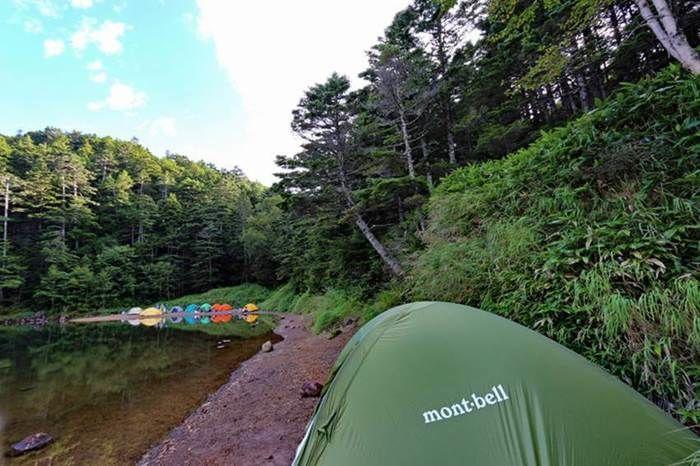 池のほとりで傾いたテント