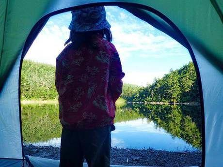 テントから池を眺める子供の後ろ姿