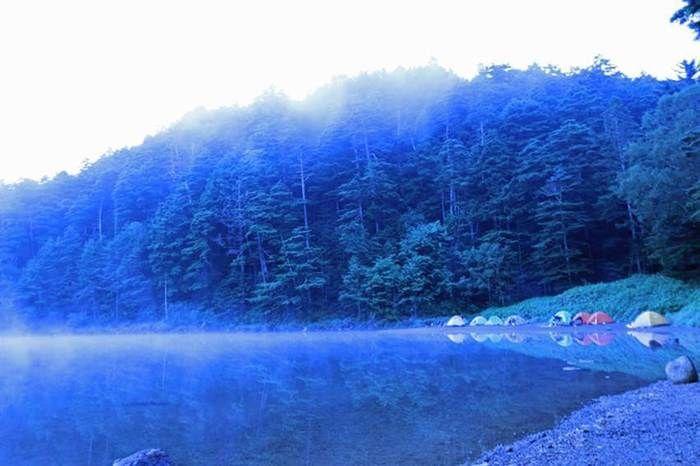 朝霧が幻想的な湖のほとりのキャンプ場