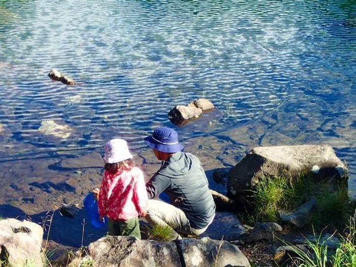 雄池で水を汲む親子の後ろ姿