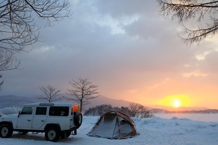 朝日と雪の上に張られたテント