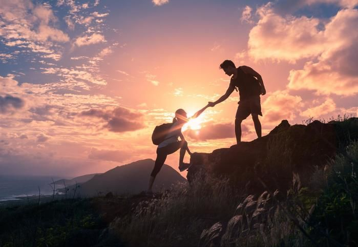 夕日に照らされる崖を登る女性の手を引っ張る男性