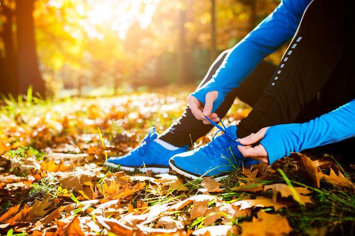 落葉の上に座り靴紐を結ぶて足元